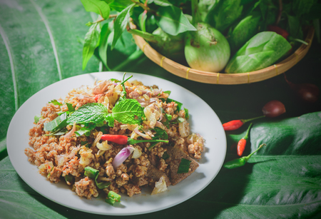 Spicy minced pork mix Zanthoxylum rhetsa with fresh vegetables in dark moody tone, Northern food of Thailand.. 版權商用圖片