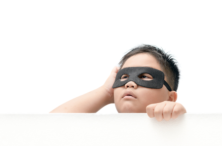 masked child appeared from below with an expression of surprise isolated on white background.. Stock Photo