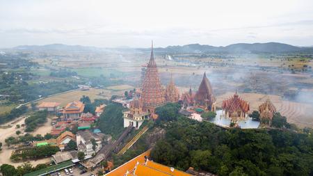 Landscape of Wat Tham Suea, Kanchanaburi Thailand with Smoke from burning rice stubble on background Editorial