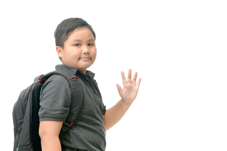 Asian boy student going to school and waving goodbye isolated on white background, back to school concept.
