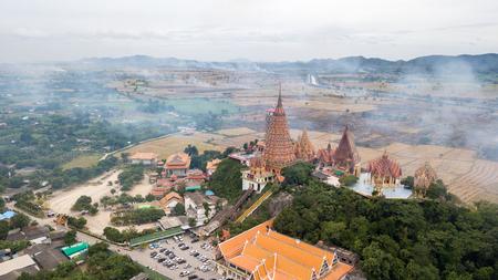 Landscape of Wat Tham Suea, Kanchanaburi Thailand with Smoke from burning rice stubble on background. Stock Photo