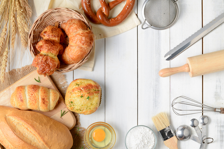 Homemade breads or bun, croissant and bakery ingredients on white wood background, breakfast food concept top view and copy space Imagens