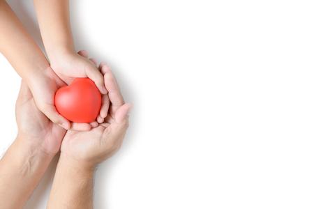 Manos de adultos y niños con corazón rojo aislado sobre fondo blanco, concepto de seguro de salud, amor y familia, día mundial del corazón