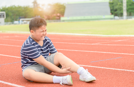 Obese boy feeling pain after having his calf pain on the track, Sport exercising injury concept