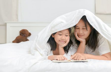 Mother tells a story to his daughter on bed before sleep, education concept.