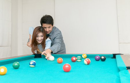 Happy couples are playing billiards in home, recreation and leisure concept. Фото со стока