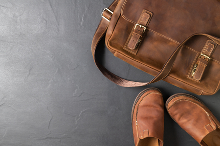Leather Vintage bag and leatrher Casual Shoes on black stone background with copy space, accessories costume concept.