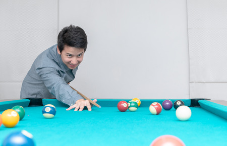 Asian man playing billards, sport and recreation concept.