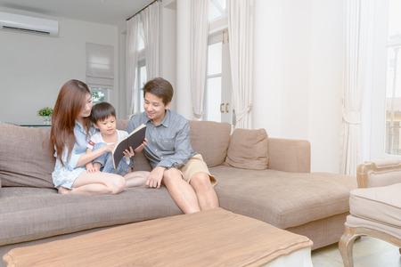 Fröhliche asiatische Familie, die zu Hause im Wohnzimmer ein Märchenbuch liest, Lern- und Bildungskonzept..
