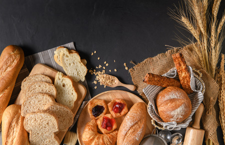 Homemade breads or bun, croissant and bakery ingredients on black stone background, breakfast food concept top view and copy space.