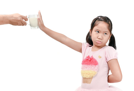 Bored kid girl with expression of disgust against fresh milk isolated on white background, Refusing food concept. 版權商用圖片