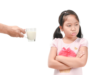 Sad girl refuses drink a fresh milk isolated on white background, Health care concept.