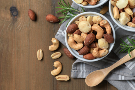 salted cocktail nuts in cup on wood background, snack food concept and top view with copy space.