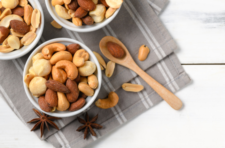 salted cocktail nuts on white wood background, snack food concept and top view with copy space. 免版税图像