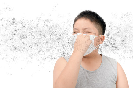 Obese fat boy wearing protective mask to protect pollution and the flu isolated on white