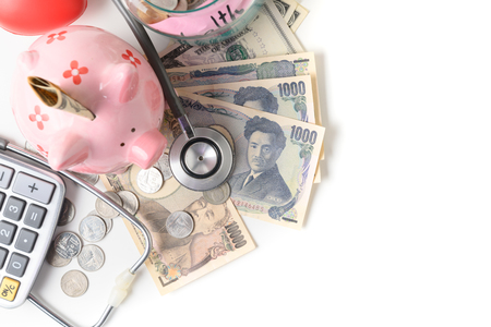 Stethoscope on Japanese yen banknote and piggy bank isolated on white Фото со стока