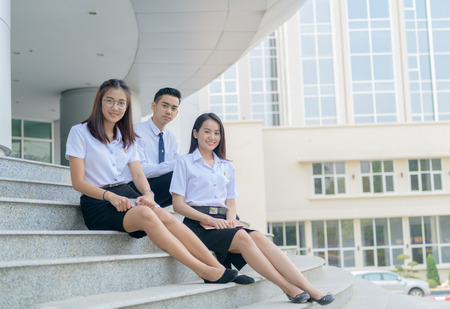 Happy asian students in uniform siting at university, education concept..
