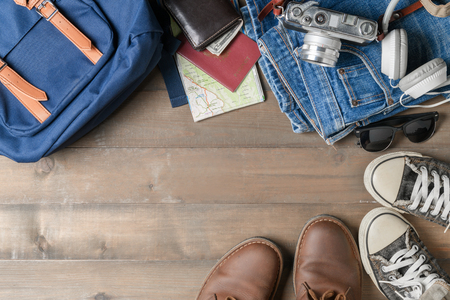 prepare backpack accessories and travel items on wood background with copy space, flat lay, top view background..