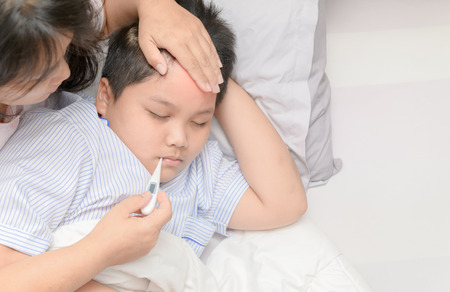 Mother measuring temperature of ill kid. Sick child with high fever laying in bed and mother holding thermometer, Healthy care concept.
