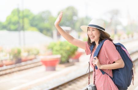 Giovane viaggiatore hipster con zaino e macchina fotografica vintage saluta o arrivederci ad un amico, viaggio, viaggio per il concetto di donna. Archivio Fotografico
