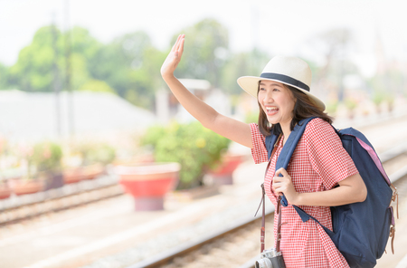 Young Hipster traveler with backpack and vintage camera say hi or good bye to friend, travel, trip for woman concept. Stock Photo