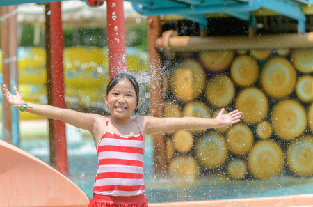 Happy little caucasian girl playing water at aquapark. summer vacation concept..