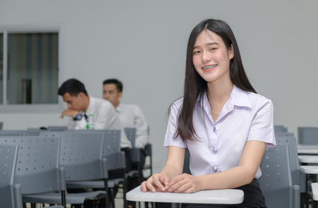 Portrait of cute asian girl student with braces on the teeth, sitting at the desk and studying at classroom university, education  concept