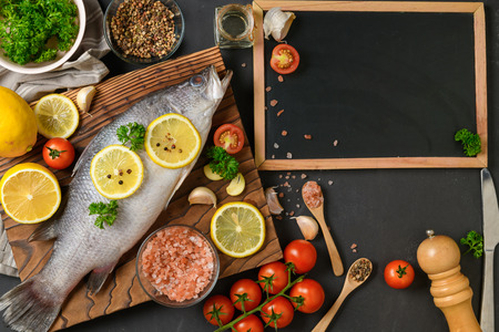 Fresh fish seabass and ingredients for cooking with blank backboard for text menu.