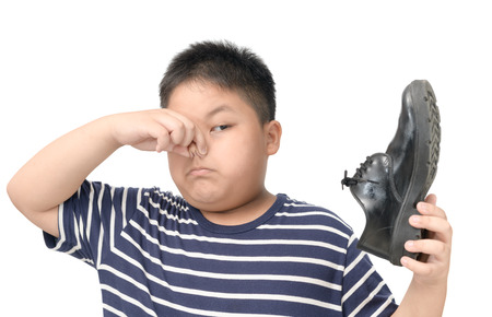Disgusted fat boy holding a pair of smelly and stinky leather shoes isolated on white