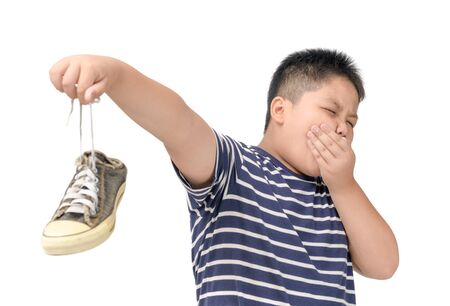 Disgusted fat boy holding a pair of smelly and stinky shoes isolated on white