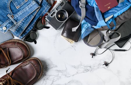 prepare backpack accessories and travel items on marble background with copy space, flat lay, top view background.