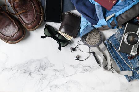 Prepare backpack accessories and travel items on marble