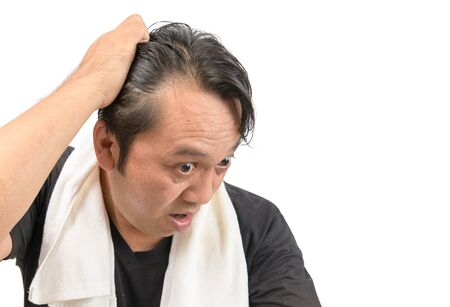 Middle-aged asian man worry about his  hair loss or alopecia and grey hair isolated on white