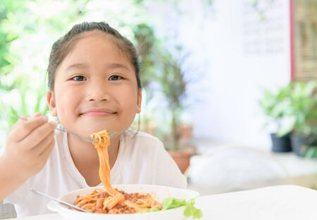 Happy girl enjoy eating spaghetti with pork sauce, food and healthy concept. Foto de archivo - 129246253