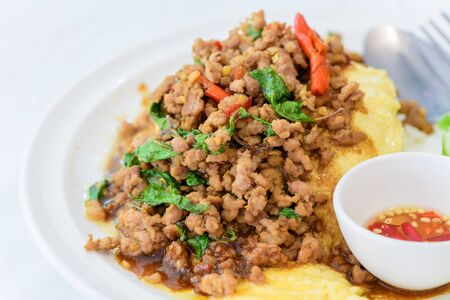 Fried basil with pork on an omelette and Fish sauce with chilli, street food and popular thai food. Foto de archivo - 129246254