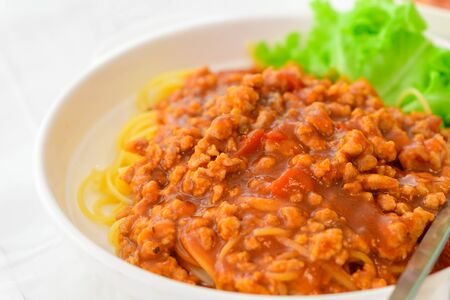 Spaghetti with pork sauce on white table Foto de archivo - 129246267