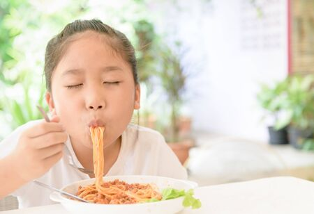 Happy girl enjoy eating spaghetti with pork sauce, food and healthy concept Foto de archivo - 129246277