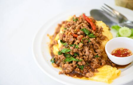 Fried basil with pork on an omelette and Fish sauce with chilli, street food and popular thai food Foto de archivo - 129246276