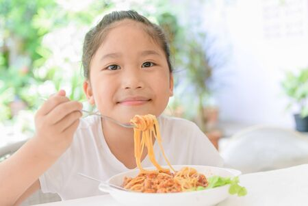 Happy girl enjoy eating spaghetti with pork sauce, food and healthy concept Foto de archivo - 129246502