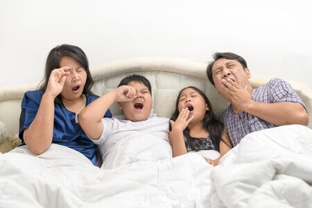 Indoor shot of family feeling sleepy while waking up early in the morning. 写真素材