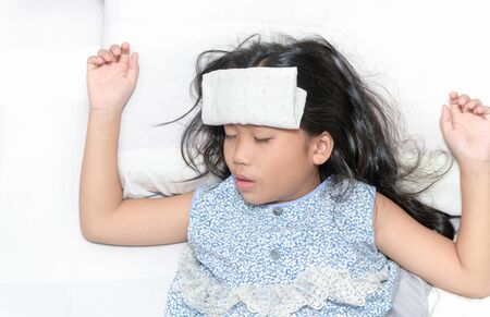 Sick child with high fever laying in bed. Compress on forehead. health care concept.
