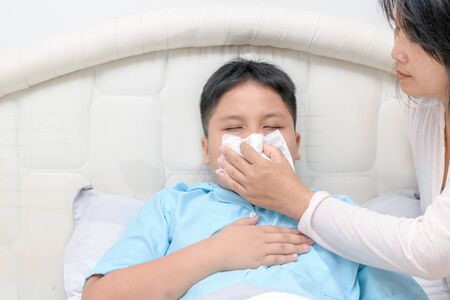 Sick asian child wiping or cleaning nose with tissue while mother helping him. Health care, fever and flu concept Stok Fotoğraf