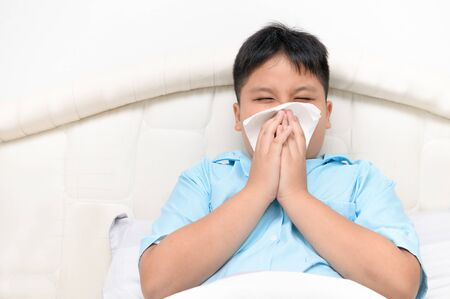 Sick child. Asian fat boy has runny nose and blows nose into tissue sitting on bed, Health care concept..
