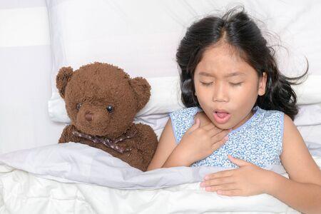 Kleines Mädchen hustet und Halsschmerzen liegt auf dem Bett mit Spielzeugbären, Gesundheitskonzept..