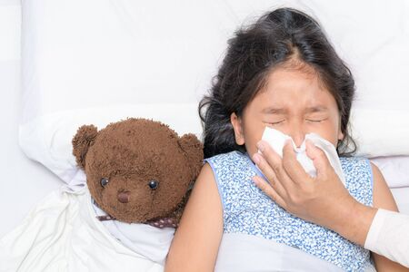 Mother blowing the nose of her daughter, sick girl lying on bed, Health care concept.
