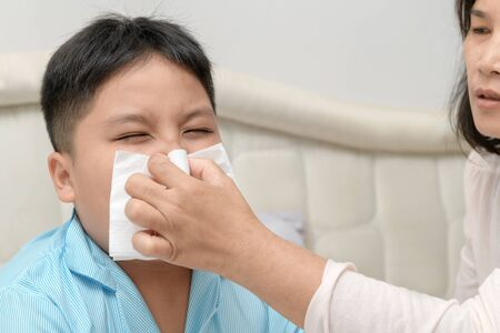 Sick asian child wiping or cleaning nose with tissue while mother helping him. Health care, fever and flu concept..