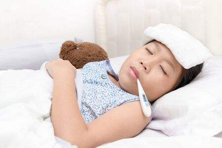 Sick girl with thermometer in mouth lying on bed, Health care concept..