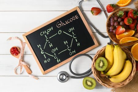Glucose molecule on blackboard with mixed fresh fruits and stethoscope on wooden white background, Diet and food science concept..