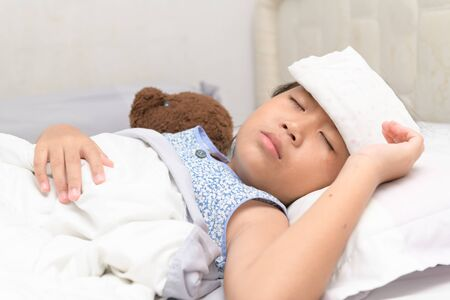 Sick child with high fever laying in bed. Compress on forehead. health care concept.. 스톡 콘텐츠