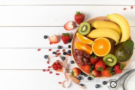 Macedonia di frutta fresca mista con fragola con stetoscopio e taccuino in bianco su fondo bianco di legno. Concetto di frutta dietetica e vista piatta e dall'alto.